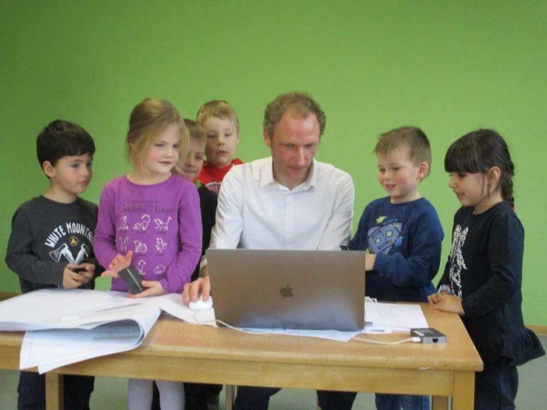 Mike Schneider in der Mitte von Kindern