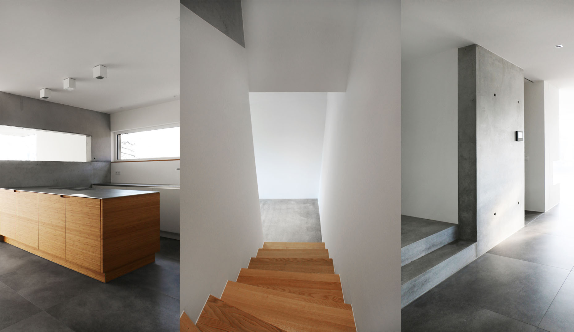Ein Bild einer modernen Küchenzeile, einer Treppe und eines Eingangsbereichs in Betonoptik