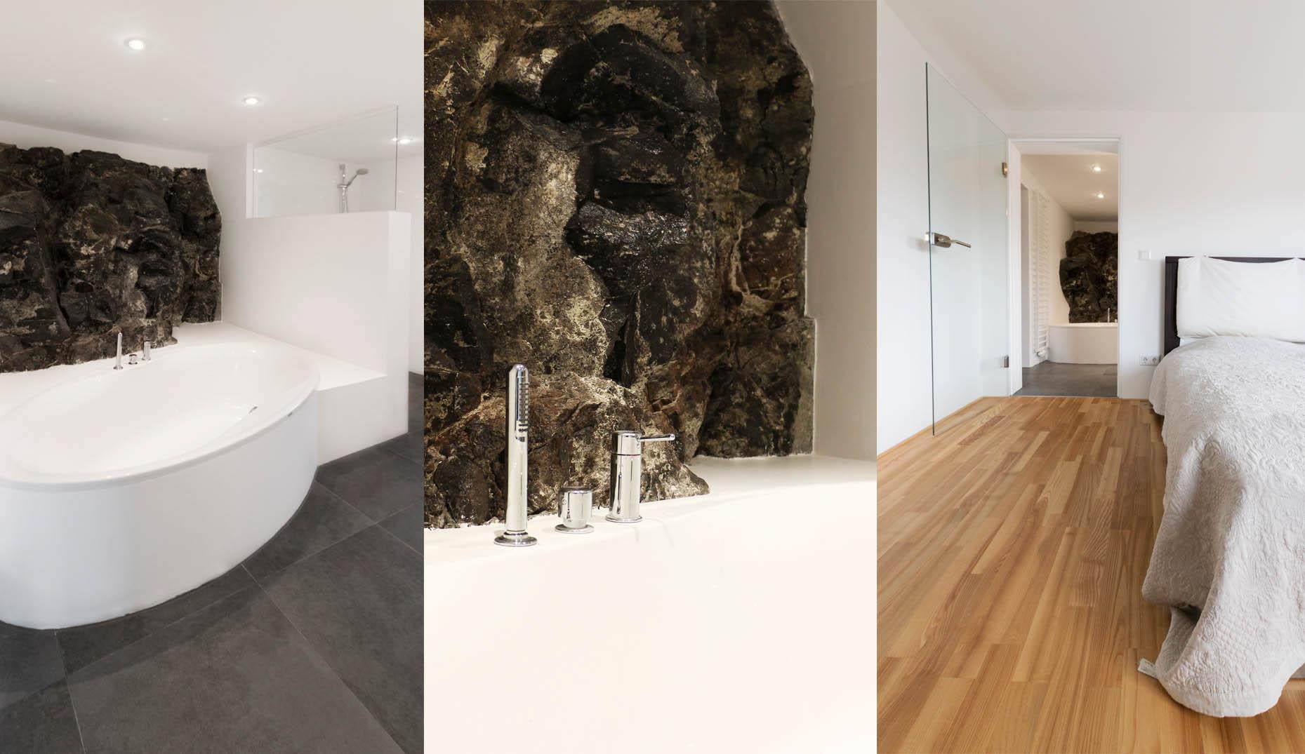 Eine ovale Badewanne mit Steinelementen